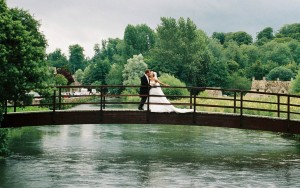Bride and Groom on bridge outside Swan Hotel in Bibury